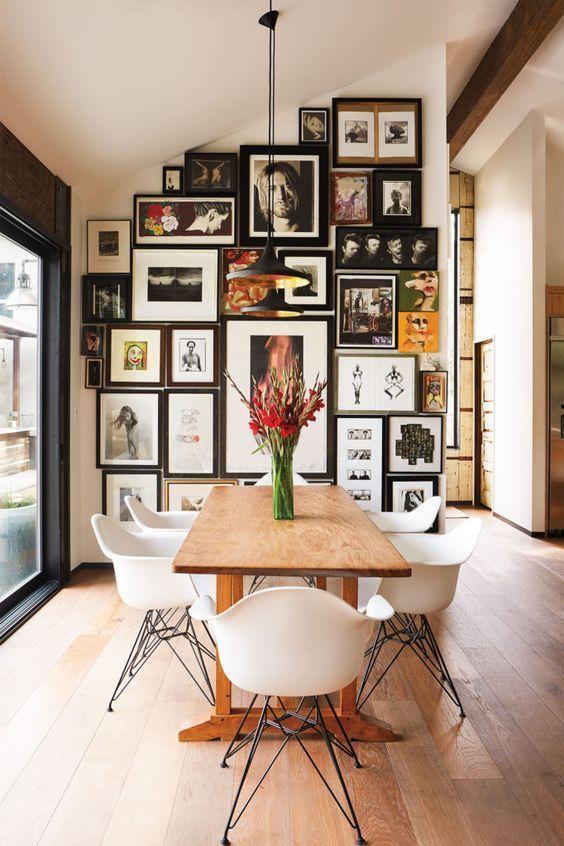 Eine sehr volle Galeriewand mit Holztisch und Stühlen im Stil