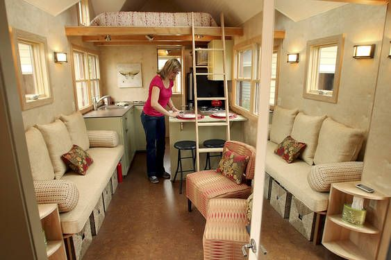 """Seattle Tiny Homes:     """"After years spent as a private contractor drawing floor plans for regular-sized homes, Sharon Read started Seattle Tiny Homes, a company that specializes in eco-friendly high-end miniature homes. Sharon Read, founder of Seattle Tiny Homes, places dishes in the dining area in the Ballard model home that she created. (Article)"""