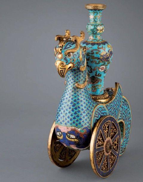 CHINE - Epoque QIANLONG (1736 - 1795) Rare récipient en forme de phénix « zun » en bronze doré et émaux cloisonnés posé sur deux roues. Le plumage en bleu turquoise et bleu foncé, les ailes et la queue… - Blanchet & Associés - 11/06/2015