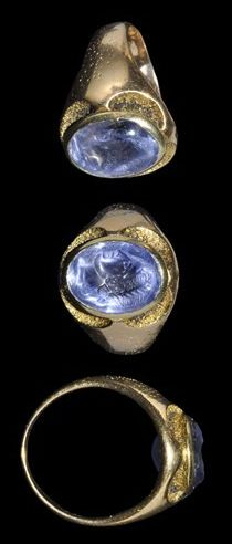 Circa 16th century AD. A gold finger ring with plain hoop expanding to an elliptical bezel holding a Roman sapphire intaglio depicting the bust of Constantius I (250 - 306 AD), son of Constantine I, set within a cell retained by four scalloped recesses; the underside of the bezel open to display the translucence of the stone.