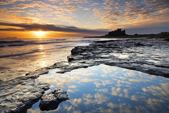 The sun rises over the coast near Bamburgh Castle, Northumberland