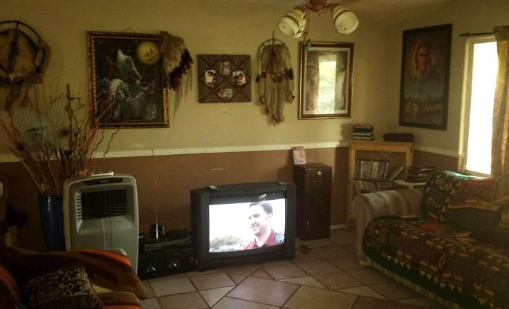 cluttered living room Southwest fake Indian art dream catchers TV is on poor bad home staging Phoenix Arizona house for sale photo