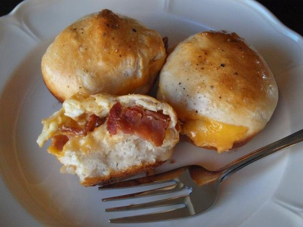 Breakfast muffins made with biscuit dough, scrambled eggs, cheese and bacon/sausage/ham.