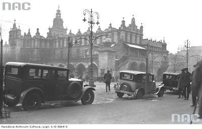 Taksówki na postoju na Rynku Głównym w Krakowie. W głębi widoczne Sukiennice. Data wydarzenia: 1931-01