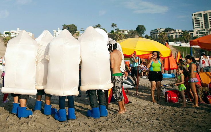 Mascots in condom costumes hand out prophylactics during International Condom Day at Agua Dulce beach in Lima, Peru