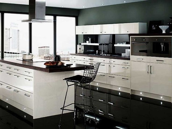 Kitchen tiles black with white wooden color cabinets and rectangle shape white kitchen island also black granite countertop