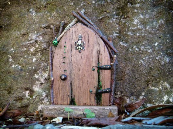 Entice the fairies into your garden with this gorgeous fairy door adorned with upcycled jewellery. With its pair of handmade hinges, intricate twig framework and a delicate sprinkling of green glitter, what fairy could resist? A green bell is suspended from a coil of rusty wire, ready for their visitors to ring. This door will suit your fairies if they have a hankering for privacy as it can only be opened by magical folk... Place this door in your garden or home to add a little fairy magic…