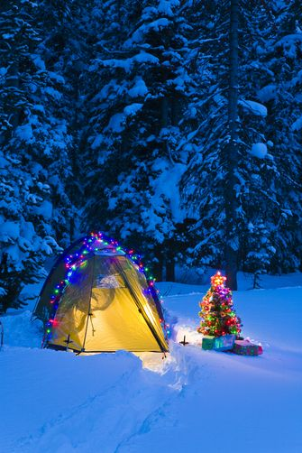 Decorated camp tent and small Christmas tree with packages outside in snow in Grand Teton National Park, Wyoming - National Geographic Creative.