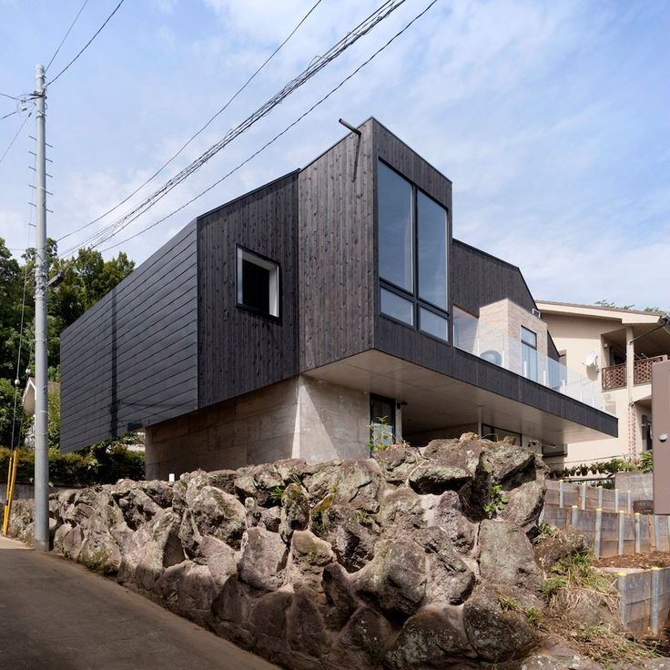 A angular, blackened wood structure sits atop two concrete blocks to form this house in Japan's Kanagawa Prefecture, designed by Cubo Design Architect