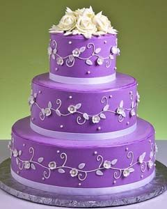 Lovely three tier purple round fondant wedding cake decorated with intricate scroll work and handcrafted white flowers. Crowned with a white roses wedding cake topper. From www.jacquespastries.com