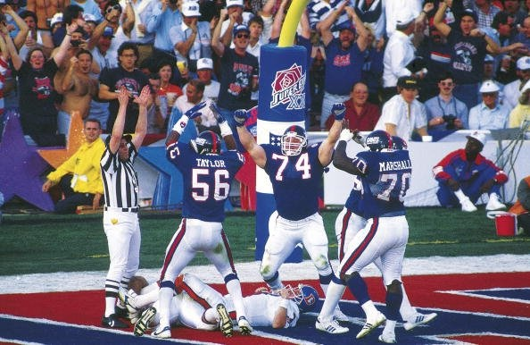 Super Bowl XXI  January 25, 1987 in Rose Bowl  New York Giants' George Martin sacks Denver Broncos' QB John Elway in the end zone resulting in a safety, the only scoring of the second quarter. Teammates Lawrence Taylor, Erik Howard and Leonard Marshall celebrate with Martin after taking Elway down. The Giants trail 10-9 at half in the narrowest halftime margin in Super Bowl history before beating the Broncos, 39-20.  (Getty Images)