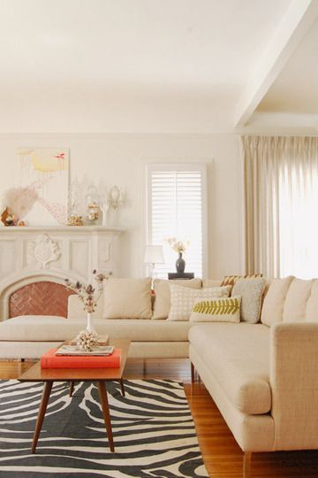 not typically a fan of all white - or cream or whatever - but I like the usage of natural elements: animal print rug, leaf on pillow...