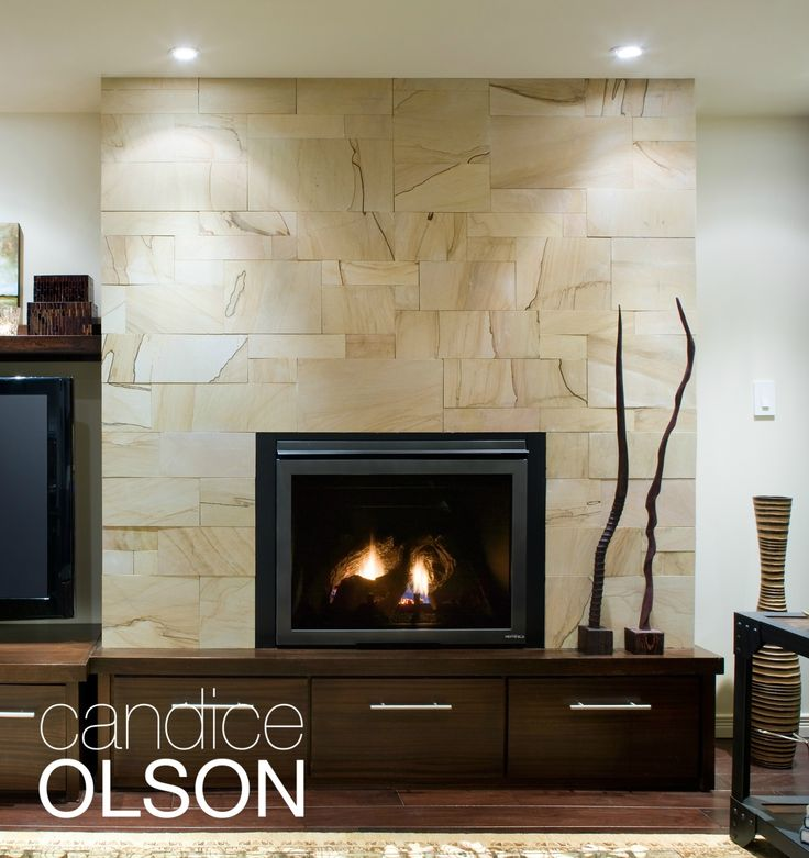 A stunning sandstone-tile fireplace surround stretches all the way to the ceiling. The tile is set close without grout to take advantage of the pattern, which gives the effect of wood grain. Custom storage doubles as a hearth. #candiceolson