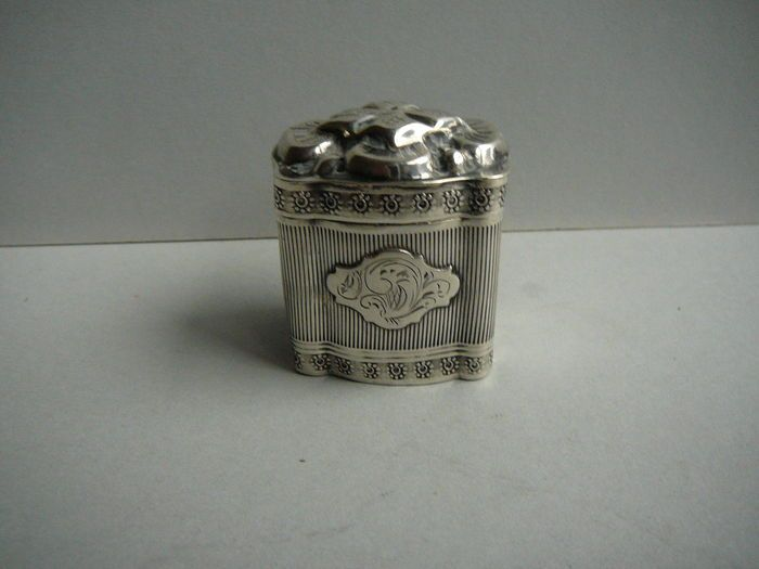 Zilveren lodereindoosje Nederland 1861  Antiek zilveren lodereindoos in sierlijke gecontourneerde vormgeving.Deksel in zgn kussenmodel met gedreven florale voorstelling.Rondom versierd met banddecoraites met bloemmotieven en klassieke ribpatronen.Alle zijden zijn verlucht met appliques met gravé decors. Maten:45 x 40 x 30 cmGewicht:: 25 gramMerken: Nederlandse leeuw 2 Minervahoofd Meesterteken K10 in vierkant Jaarletter b = 1861Conditie: Luxe stevige doos met prima werkend scharnierdeksel…