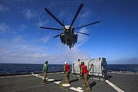A CH-53E Super Stallion helicopter assigned to Marine Medium Tiltrotor Squadron (VMM) 162 (Reinforced), approaches the fleet replenishment oiler USNS William McLean (T-AKE 12) to transport cargo to the Wasp-class amphibious assault ship USS Iwo Jima (LHD 7) during Helicopter Support Team...
