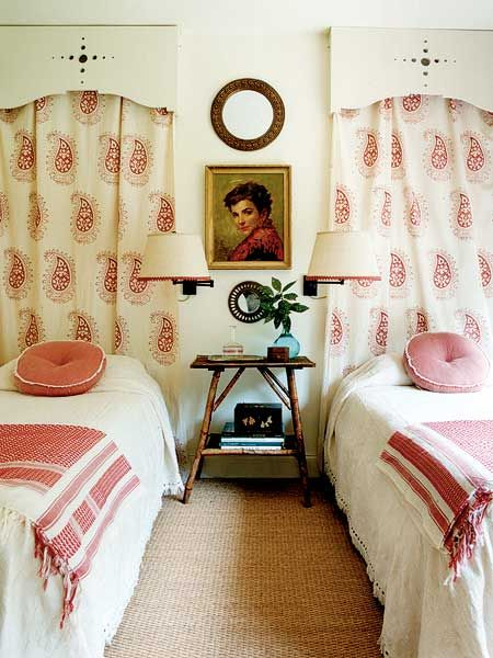 """A small guest or girl's room gets a dramatic treatment with paisley """"headboards"""" topped by homemade valences created by drilling plywood with different-size bits. An arrangement of flea market mirrors and a painting fills the empty wall space between the beds with flair. (Photo: Megan Thompson)"""