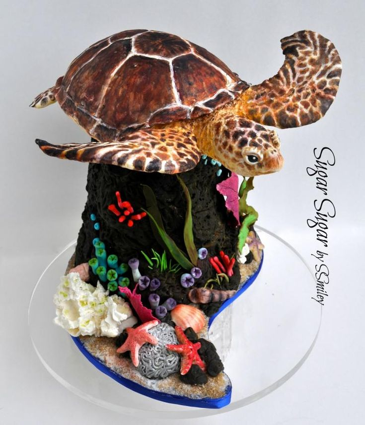 Sea turtle made from Rice Krispy Treats covered in modeling chocolate and colored with petal dusts and alcohol. Everything else is made of fondant or gum paste. Because the young lady wanted to keep the turtle, a couple of dozen matching cupcakes...