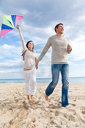 couples with kites | … autumn winter spring couple embracing and running on beach a kite fly