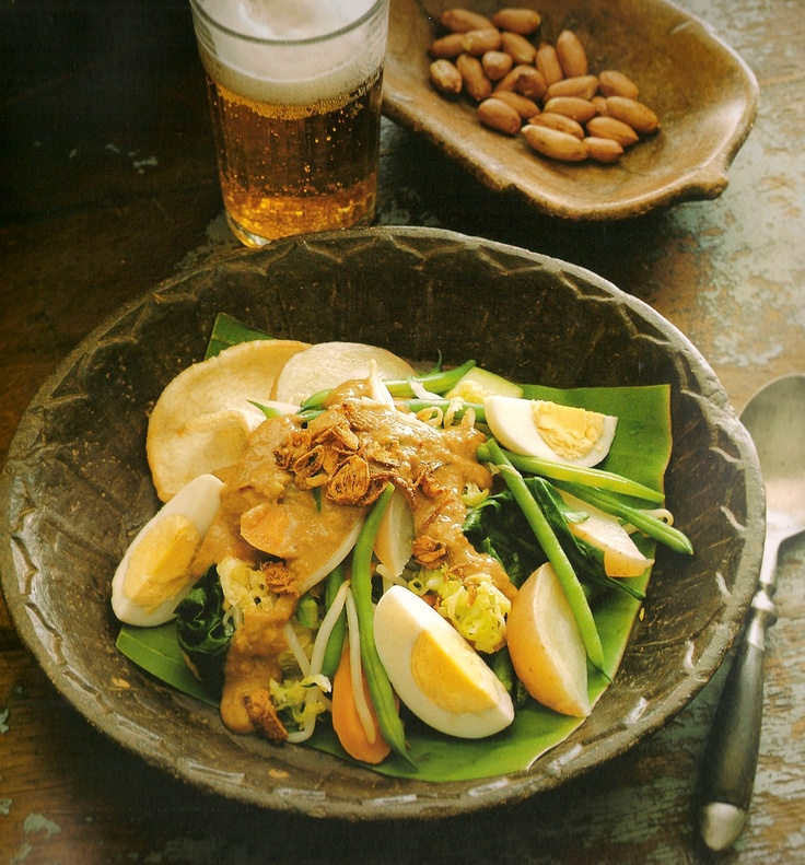 Indonesian Food. Gado Gado.               A variety of blanched vegetables, tempeh, tofu a boiled egg and a potato, covered with spicy peanutsauce and fried onions. Serve with kroepoek (shrimp crackers), and lontong (sticky rice cubes).     Selamat Makan (bon appetit).