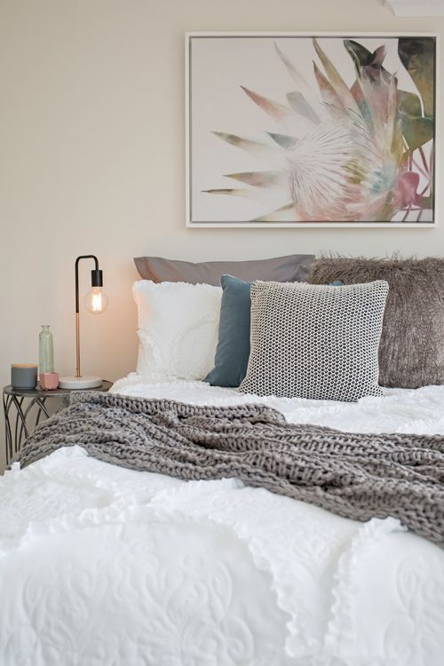 Modern guest bedroom, soft colour palette, white ruffled bedding, grey cable knit throw blanket, protea canvas