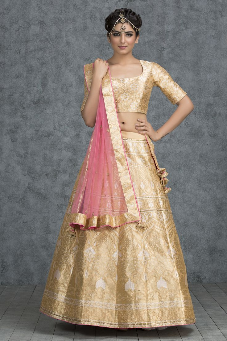 Presenting this golden mist banarasi silk lehenga passionately crafted to make you feel exquisite. It comes with matching golden mist banarasi silk choli with a deep round neck and long sleeves. The contrasting strawberry shortcake tulle dupatta with a silk brocade border is a definite stunner.