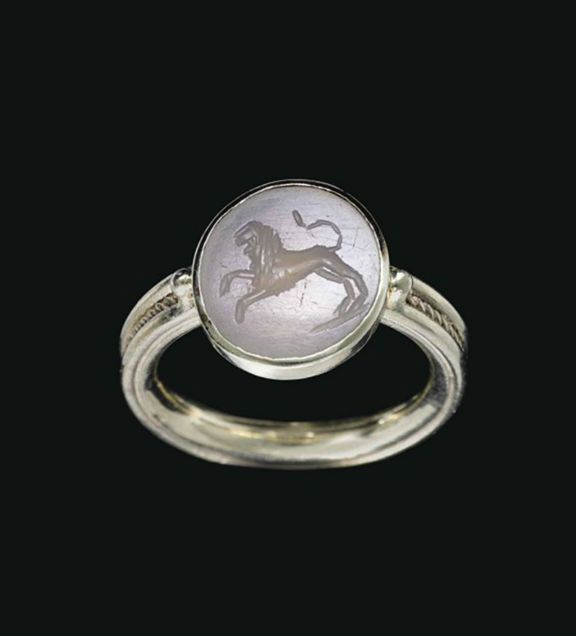 A ROMAN CHALCEDONY RINGSTONE  CIRCA 2ND-3RD CENTURY A.D.  The flat, circular stone engraved with a lion leaping to the left on a short groundline, its tail raised; mounted as a ring in a modern white gold setting