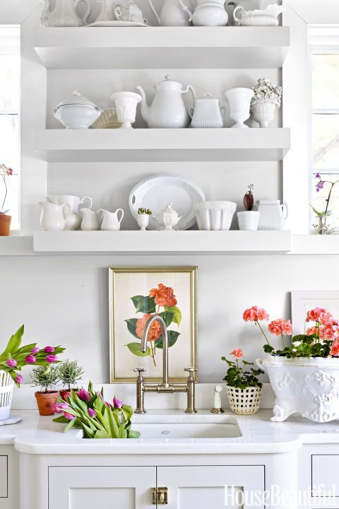 FLOWER-FILLED MUDROOM– A mudroom doubles as a place to arrange flowers, thanks to shelves filled with ironstone vessels. The homeowner's favorite pale pink geraniums inspired some of the hues in the feminine townhouse. Click through for the entire gallery and for more spring decorating ideas.