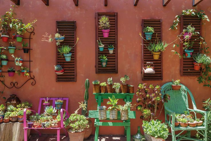 Patio rústico en terracota con toques de color verde y violeta, lleno de plantas en macetas de objetos reciclados.