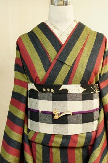 黒と赤とアッシュイエローの幅広ストライプがレトロモダンなネル素材のウール単着物です。Wide stripes of red and yellow ash black wool single kimono fabric panel is retro-modern.