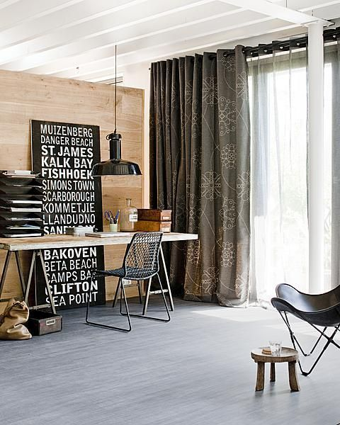 A tough work area requires a strong fabric with decorative stitching. These curtains give the room a small dose of frivolity. The semi-transparent curtains behind it, provide privacy and a soft light.