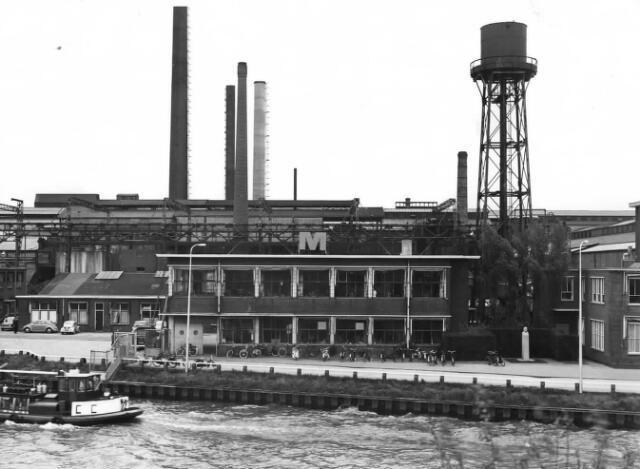 1955-1965. Gezicht op een gedeelte van de fabriek N.V. Nederlandse Staalfabrieken DEMKA voorheen J.M. de Muinck Keizer (Havenweg 7) te Utrecht, vanaf de spoorbrug over het Amsterdam-Rijnkanaal, uit het zuidwesten; in het midden het gebouw van de loonadministratie (begane grond) en de personeelsruimte (verdieping) met rechts daarvan de watertoren en een deel van het hoofdkantoorgebouw; links het voormalige laboratorium en de ingang van het fabrieksterrein met op de achtergrond de schrootbaan.