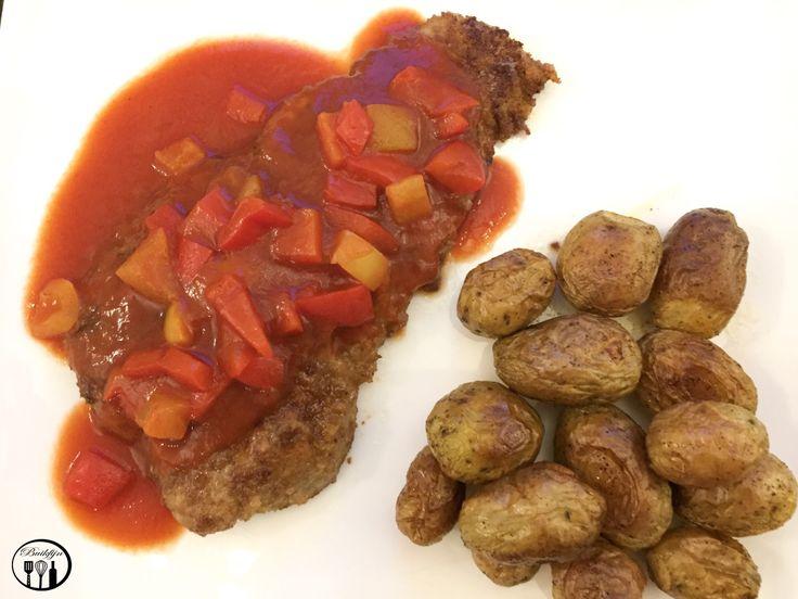 Ingrediënten voor 2 personen  2 naturel schnitzels  60 gram glutenvrij paneermeel (Peak's of Schar)  60 gram glutenvrij bloem  200 ml neutrale bouillon  4 el ketchup  1 ei  1 rode paprika  1 groene paprika  1 tl paprika poeder  1 el azijn  2 el knoflookolie  1 blikje tomatenpurree  1/2 el maizena    Bereidingswijze  1. Snijd de paprika's in blokjes. Verwarm een koekenpan en voeg 1 eetlepel knoflookolie toe. Bak de paprika´s een paar