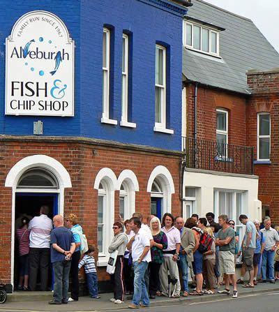 Aldeburgh Famous Fish and Chip shop-Aldeburgh is a small seaside town on East Suffolk Coast notable for its Blue Flag shingle beach and fisherman huts with freshly caught fish and seafood for sale. Ate fish and chips on the beach here many times and the queue of people says it all!