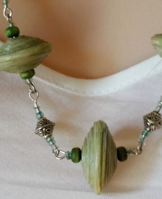 Green, saucer shaped, paper bead, wooden bead and silver spacer beads necklace. $45.00