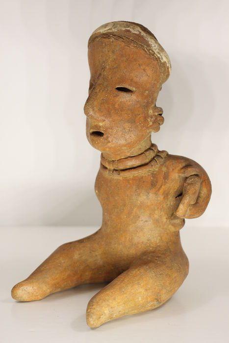 Een pre-Columbiaanse antropomorfe beeldje in aardewerk - hoogte: 19.7 cm  Een heerlijk zittende vrouwelijke terracotta figuur (Nayarit San Sebastián stijl). Gemaakt van eartenware geschilderd met roodachtig bruin slip en gepolijst overeenkomstig met de overblijfselen van een patroon van negatieve weerstaan. Holle met vent-gat boven op het hoofd.Typisch langwerpige visage en ingesneden coiffure. Haar gezicht toont verfijnde contouren een prominente neus ingesneden ogen en mond open. Ze heeft…