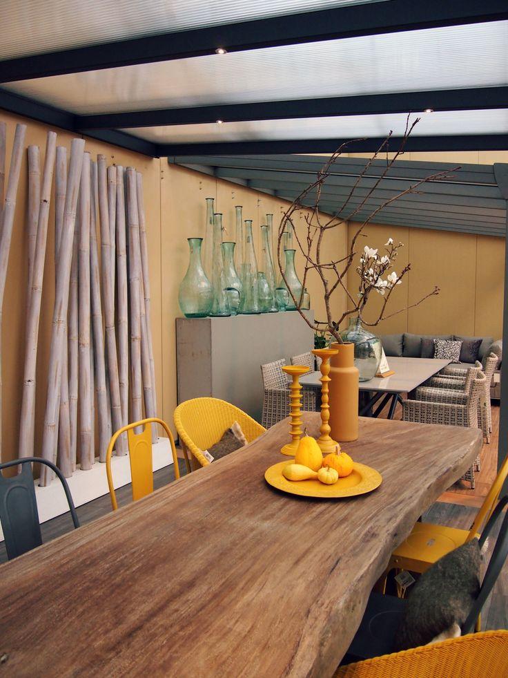 Met een robuuste houten tafel, #gevlochten #rieten stoelen en #gele accessoire krijgt je veranda een diverse uitstraling.