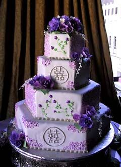 Purple four tiered hexagon cake with Chinese markings. With green stems and purple flowers and roses.