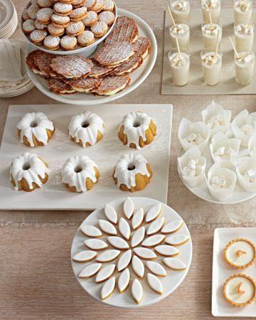 all-white dessert buffet...  love the flower arrangement of the almond shaped cookies