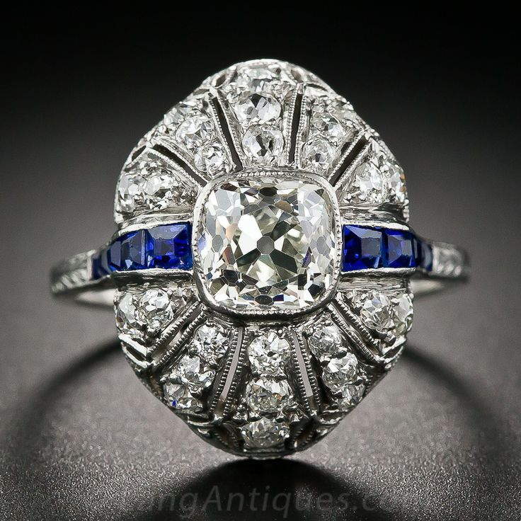 A gorgeous diamond dinner ring or engagement ring from the 1920s. An oval cushion-cut diamond is bezel set into a bombe' shape setting which is delicately pierced and finished with fine milgraining. Numerous old mine-cut diamonds and rich blue calibre sapphires enhance the superb antique 1.30 carat cushion-cut center diamond. A crisp, original example of Edwardian detailing transitioning into the Art Deco period.