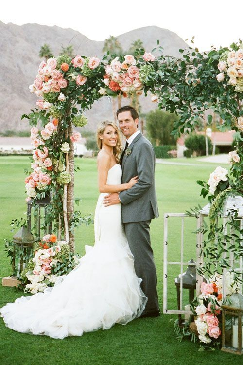 ceremony arch covered with peach and coral flowers and lush greenery