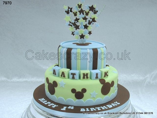 Unusual colours for this Mickey Mouse themed 1st birthday cake.  Decorated in green, blue and brown with simple strips on the upper tier, and mickey silhouettes around the cake. Named building blocks and wired starburst cake topper