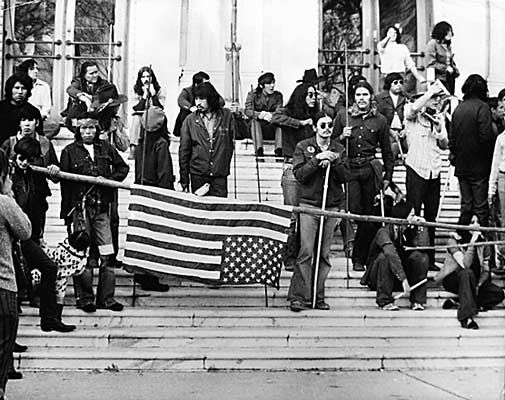 Native American activists occupy of the Bureau of Indian Affairs building in 1972. The takeover occurred from November 3rd and lasted until November 9th. Soon after a group of about 500 Native People arrived at the Bureau of Indian Affairs to negotiate better housing and other issues, a perceived doublecross served as the catalyst for the takeover. Photo credit: Does anyone know who the photographer is?