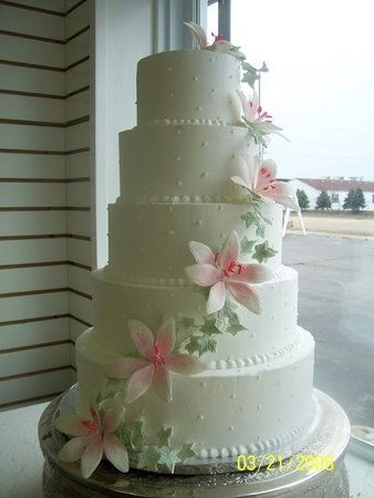 white cake with pink stargazer lilies