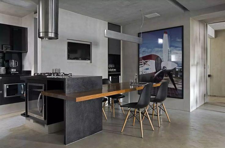 Stile minimal industriale con eleganti sedie nere, tavolo suspendato in massello, pavimento in cemento e accenti in acciaio
