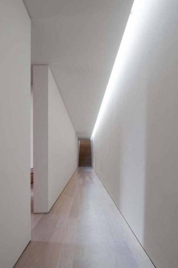 The lighting quality inside this minimalist corridor provides a directionality through the axis of this space.: Cove Lighting, Interior, Hallways, Corridor 走廊, Garage, Corridor Entrance