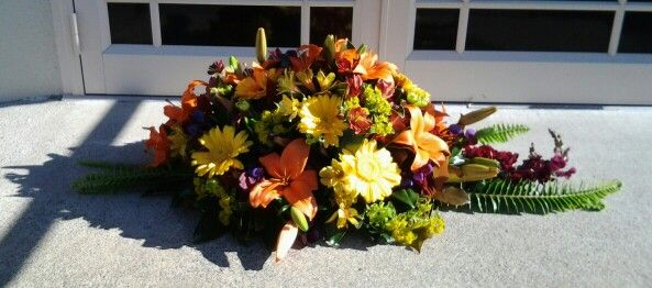 Bright and beautiful mix of bloom in the casket spray www.flowerz.co.nz
