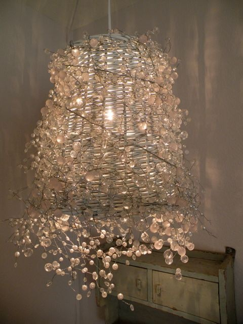 A wire form (office trash can) a hanging light fixture and a glass/crystal garland (that you can find in craft or floral stores)  Voila! Your very own chandelier!