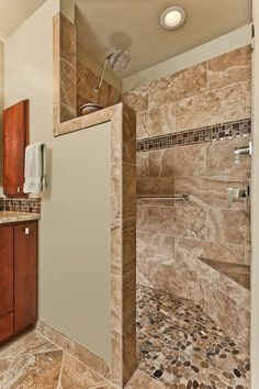 the traditional shower has been removed and this beautiful walkin open shower with seat stone flooring tile walls mosaic band and beaut