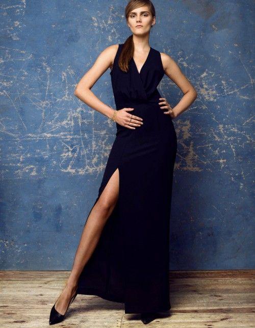 Długa klasyczna sukienka zapina z tyłu na suwak. Dostępna w kolorze - ciemny granat. Sukienka posiada efektywne rozcięcie. Idealna na wielkie wyjścia. Modelka ma 176 cm wzrostu i ma na sobie sukienkę w rozmiarze S Materiał, z którego uszyta jest sukienka jest uciągliwy