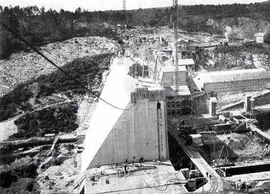 1923 1930 Chantier de construction du barrage de Guerledan. De type barrage poids en béton. Placé sur les eaux du Blavet, il mesure 45 mètres de haut au-dessus du talweg (au total 54,6 m sur fondation), 206 mètres de longueur de crête, 1,50 m de largeur de crête, 33,50 m de largeur à la base (soit un volume de 110 000 m3) et retient un volume de 55 millions de m3 d'eau sur une étendue de 400 hectares, formant ainsi le lac de Guerlédan, le plus grand des lacs bretons.
